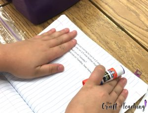 Image of students gluing problems into a notebook.